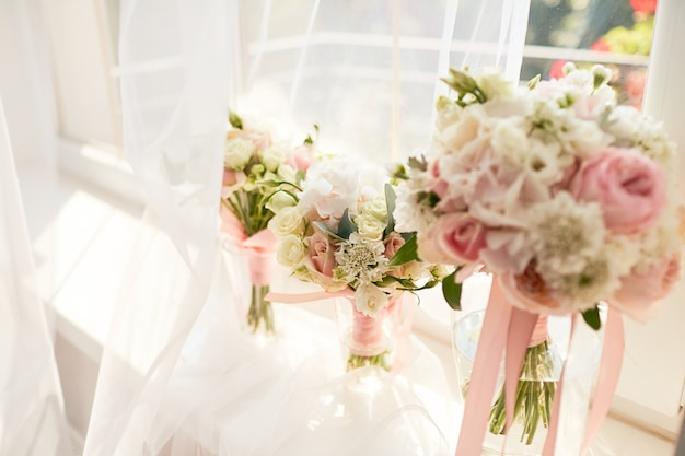 結婚式の装飾花嫁とブライドメイドの明るいピンクのバラの花束は窓の前に立つ