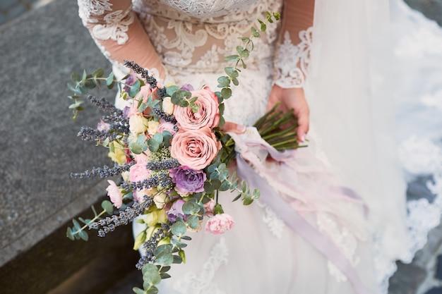 Крупный план розового и фиолетового свадебного букета в руках невесты