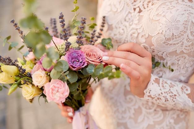花嫁の手でピンクと紫のウェディングブーケのクローズアップ