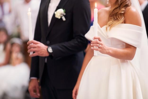 Молодожены стоят со свечами во время помолвки в церкви