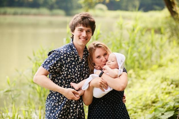 幸せな家族。ママとパパは、緑豊かな夏の公園で休んでいる彼らの幼い息子を楽しんでいます