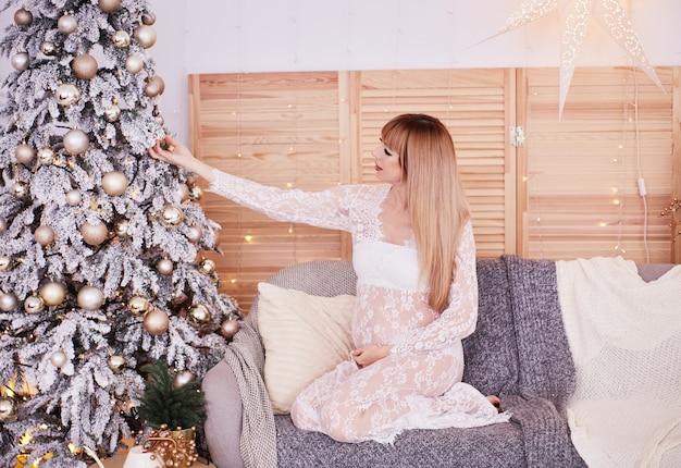 妊娠中の女性の肖像画、新年の雰囲気。魅力的な金髪の女性を期待して座っています。