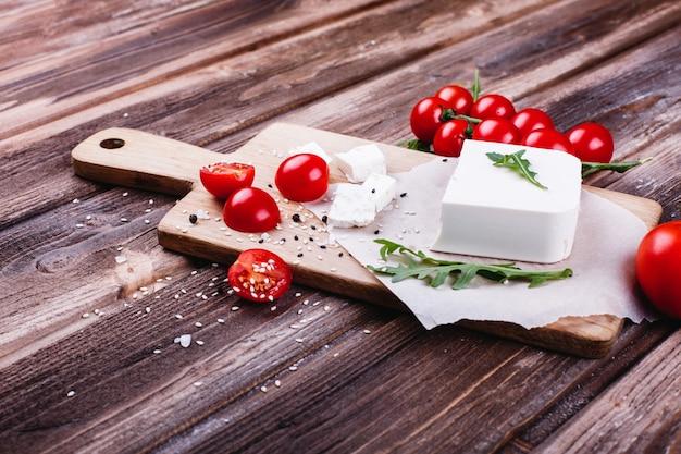 Свежая и полезная еда. вкусный итальянский ужин. свежий сыр подается на деревянной доске