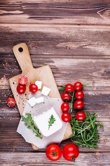 新鮮で健康的な食べ物。美味しいイタリアンディナー。新鮮なチーズを木の板で提供しています