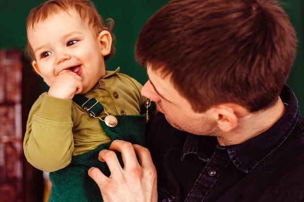 Отец держит на руках своего сына