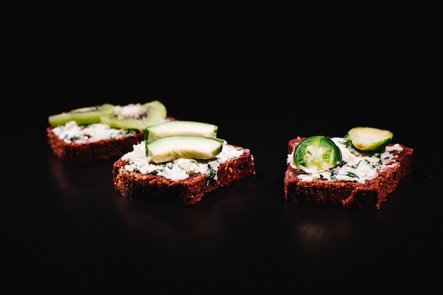 新鮮で健康的な食べ物。軽食や昼食のアイデア。自家製のパン、チーズ、アボカド