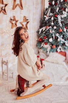 冬の休日の装飾。暖色系です。ベージュ色のセーターで魅力的なブルネットの女性