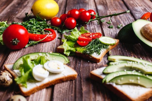 Свежая и полезная еда. идеи для завтрака или обеда. хлеб с сыром, авокадо и зеленью