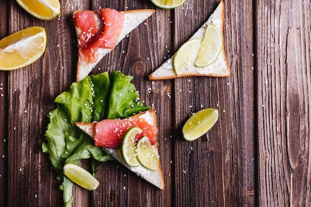 新鮮で健康的な食べ物。朝食または昼食のアイデア。チーズ、アボカド、サーモンのパン