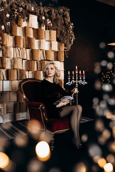 Красивая женщина в черном платье сидит перед стеной с книгами и новогодним декором