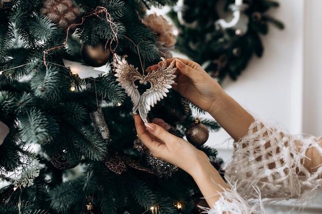 白いドレスを着た魅力的なブロンドの女性は大きなクリスマスツリーと部屋でポーズします。