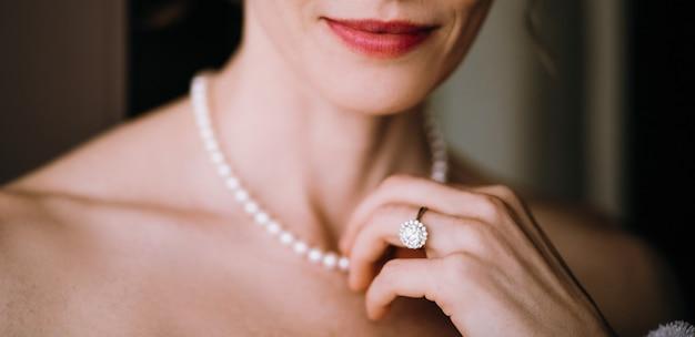 女性は彼女の首に柔らかい真珠のネックレスに触れる