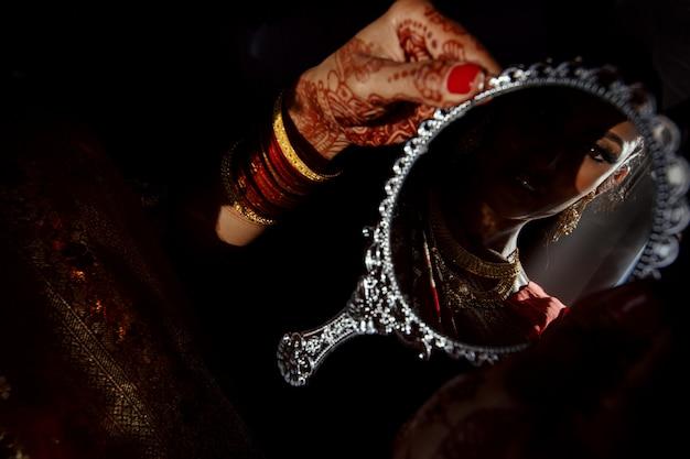 ヘナの入れ墨をしたヒンズー教の花嫁の手の中の銀の鏡