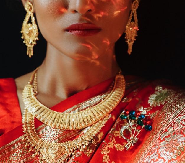 黄金のアクセントを持つ伝統的な赤いサリーのヒンズー教の花嫁の肖像画