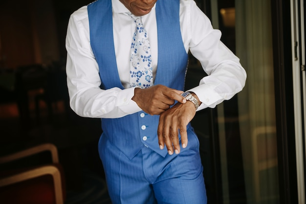 青いスーツでハンサムなアフリカ系アメリカ人の男は結婚式の準備をします