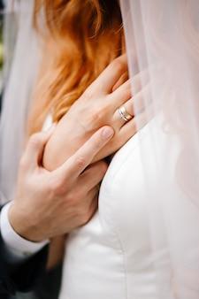 新郎は彼女の首に花嫁の手を握っています