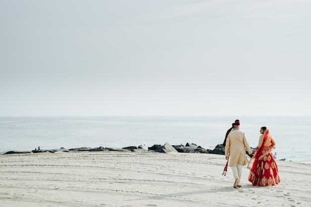 ヒンズー教の結婚式のカップルは海の海岸に沿って歩く