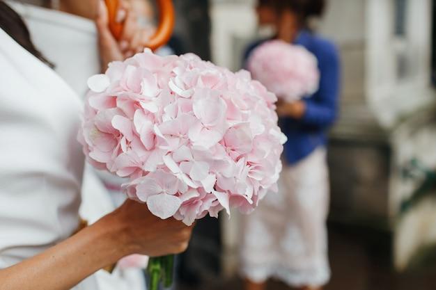 結婚式の詳細花嫁は彼女の腕に柔らかいピンクの花束を持っています。顔なし