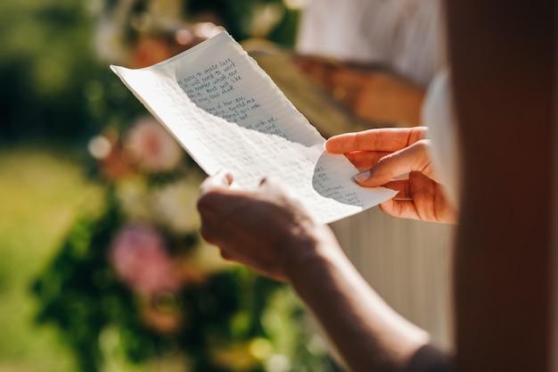 結婚式。花嫁は彼の宣誓で紙を握る