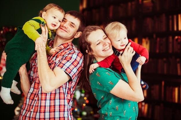 Мать и отец держат на руках своих сыновей