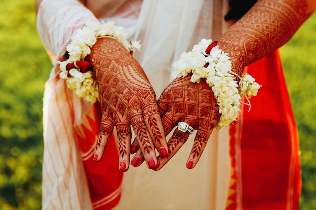 ヒンズー教の花嫁はヘナの入れ墨で覆われて彼女の手を示しています