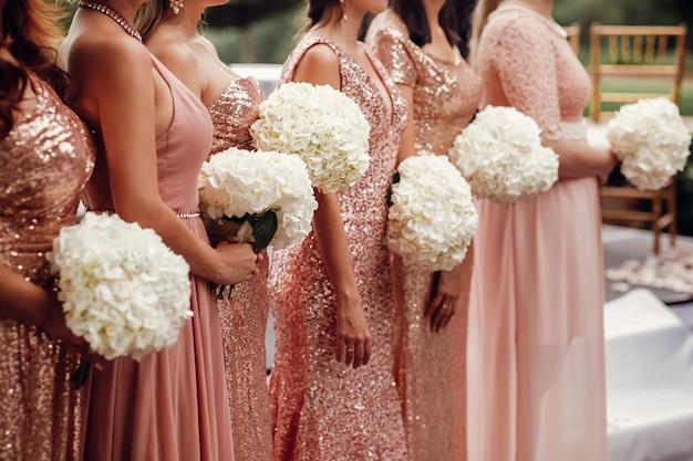 ピンクのドレスのブライドメイドは、白い花の花束と一緒に立つ