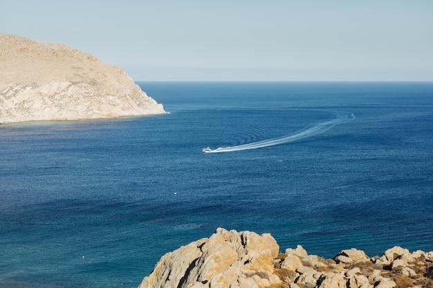 ギリシャのどこかで海を渡るボートを遠くから見てください。