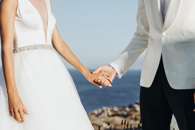 Жених и невеста в легкой летней одежде держат друг друга за руки во время церемонии