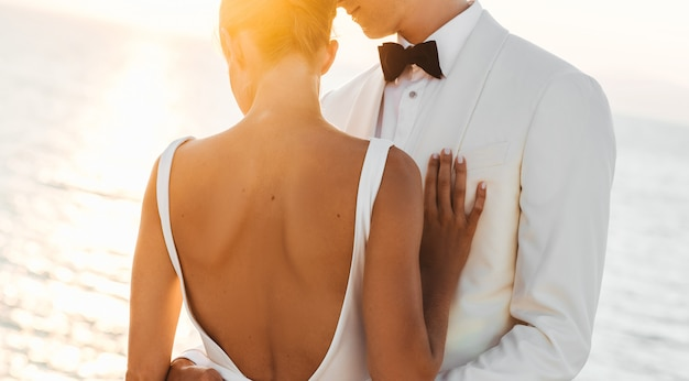 海の前に抱いて美しい結婚式のカップルに輝く夕日