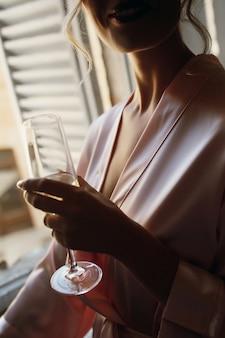 ピンクのシルクローブの魅惑的な女性はシャンパンフルートを持っています