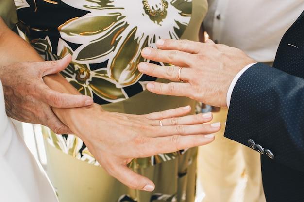 緑のドレスの老婦人は花嫁の手の入札を保持します