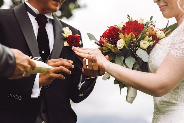 Невеста надевает обручальное кольцо на палец жениха