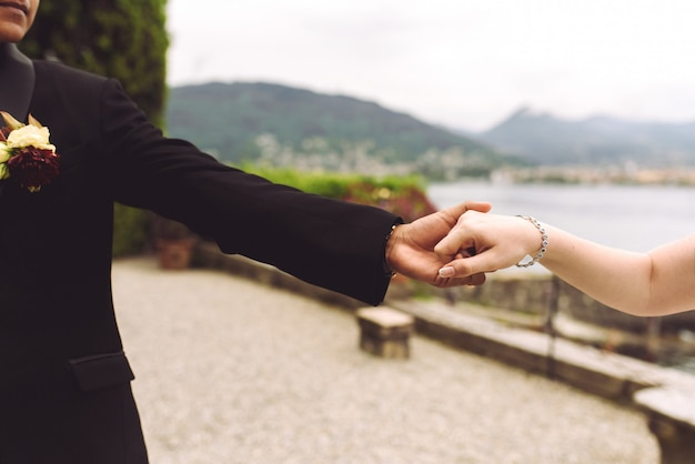 Жених и невеста держат друг друга за руки, гуляя по берегу
