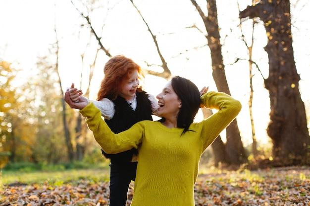 秋の雰囲気、家族の肖像画。魅力的なママと彼女の赤い髪の娘は、落ちた人の上に座って楽しんでいます