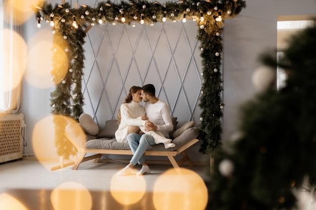 居心地の良い白い家の服の魅力的な若いカップルがクリスマスツリーの部屋でポーズ