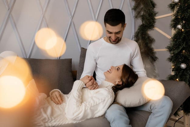 家族写真。男と女はクリスマスツリーの部屋で悪い柔らかい灰色でリラックスします。