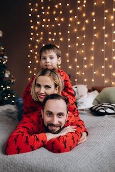 Привлекательные родители и их маленький сын в красных свитерах весело отдыхают на кровати перед рождеством