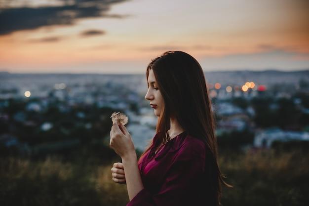 女性の肖像画自然。きれいな女性がタンポポスタンドで遊ぶ