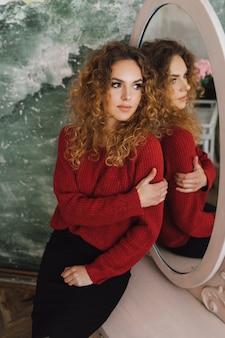 Яркая рыжеволосая девушка смотрит в зеркало