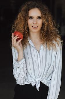 赤いリンゴを持つ若い女の子が写真をポーズします。