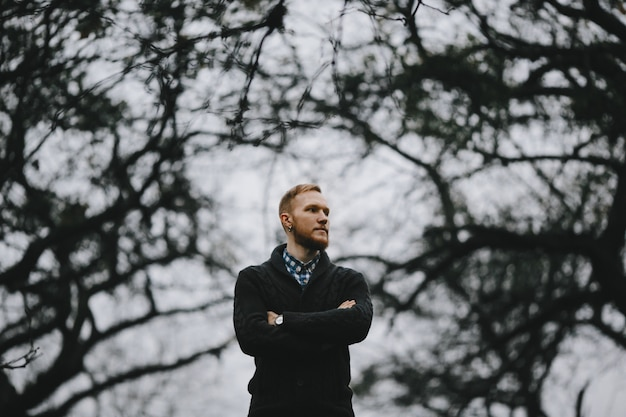 厚い秋の外に立っているハンサムな背の高い男の肖像