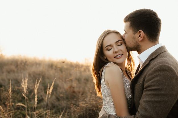 男が小麦の中で真っ直ぐに妻にキスをする