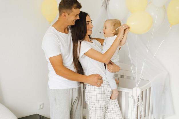 若いママとパパは彼らの幼い息子に喜ぶ