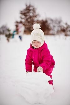 Маленькая девочка играет со снегом и радуется