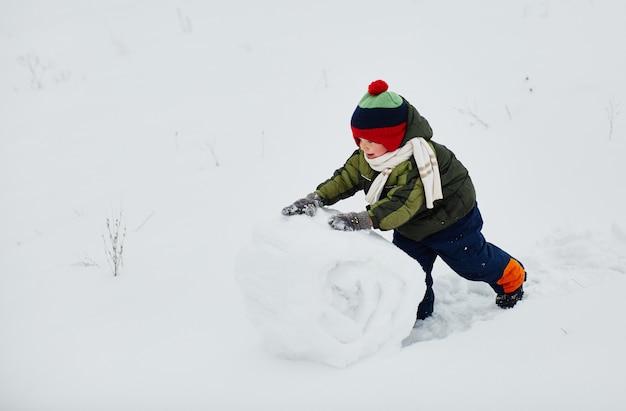 小さな男の子が雪だるまを作ります