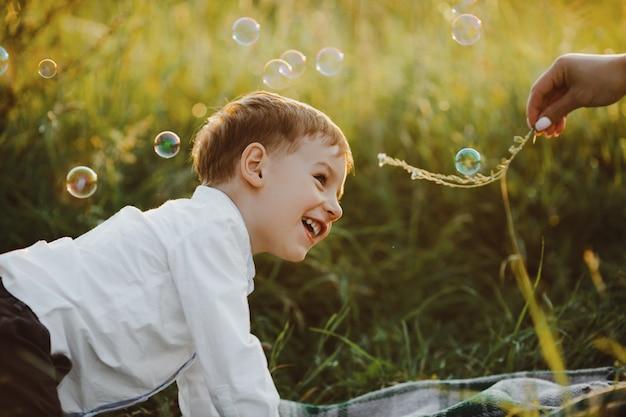 魅力的な小さな男の子は緑の芝生の上にあり、美しいを楽しんでいます