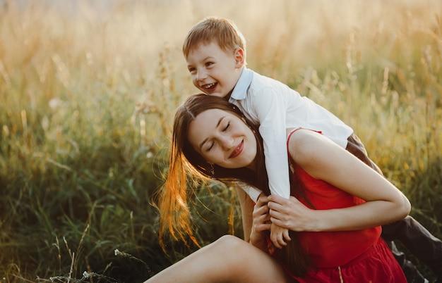 Семейный портрет, природа. очаровательная мама и сын играют на газоне б