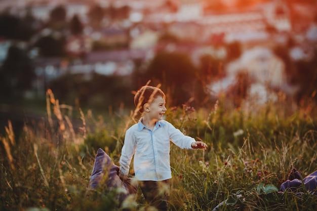 魅力的な小さな男の子は緑の芝生を渡って枕と歩く