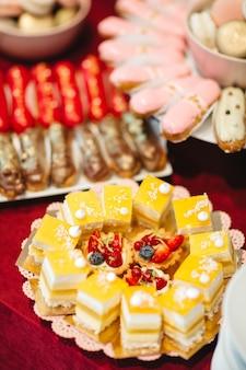 美しいケーキはお祝いテーブルの上皿にあります。