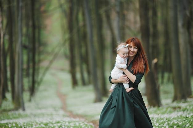 幸せな母は彼女の小さな娘をしっかりと保持します。